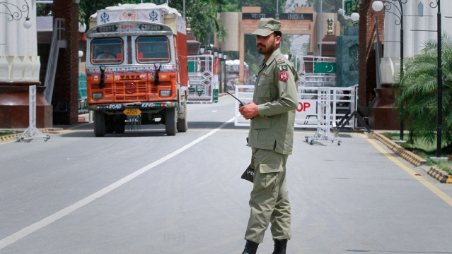 A paramilitary soldier stands guard as a truck carrying wheat crosses into Pakistan from India, at the Wagah border. (File photo: Reuters)