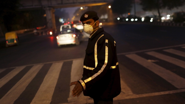 A traffic policeman wears a mask to protect himself from dust and air pollution as he signals to drivers in New Delhi, December 23, 2015. (Photo: Reuters)