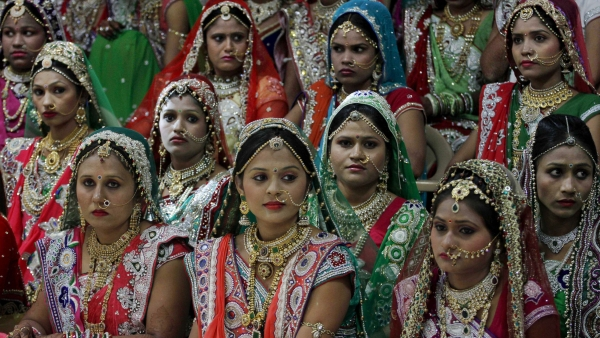Brides sit for a group photo before a mass wedding hosted by a diamond trader, Mahesh Savani in Surat.
