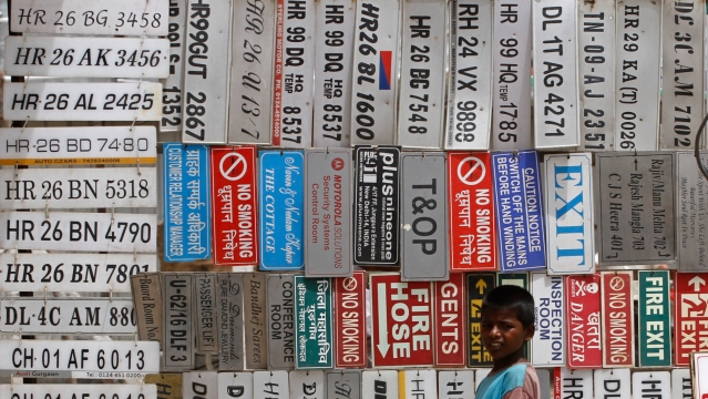 A boy stands in front of displayed car number plates and other signs at an automobile market in Gurgaon on the outskirts of New Delhi. (File photo: Reuters)