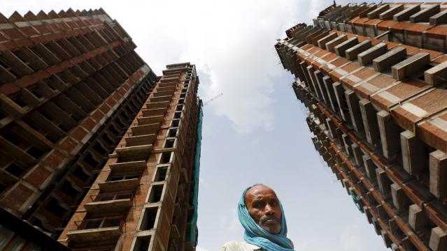 A labourer stands at the construction site of a residential complex in Noida on the outskirts of New Delhi, August 20, 2015. (Photo: Reuters)