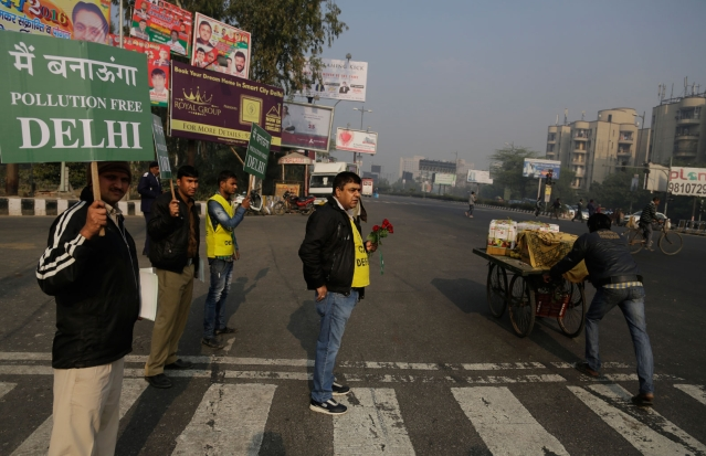A member of civil defense holds roses and others hold placards at a traffic intersection. (Photo: AP)