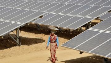 A worker walks through the installed solar modules at the Naini solar power plant in Allahabad. (Photo: Reuters)