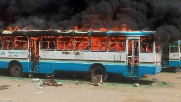 Jat community members torch a Haryana Roadways bus during their agitation for reservation. (Photo: PTI)