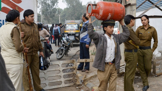 Gurgaon: A boy carries a cylinder on his head as transportation services were disrupted due to Jat community's agitation for reservation in Gurgaon. (Photo: PTI)
