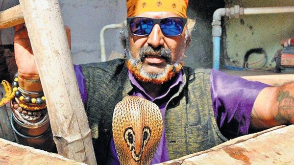 Snake Shyam with snake. (Photo Courtesy: The News Minute)