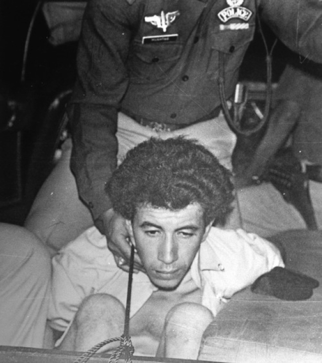 A man, said to be one of the four Pan Am hijackers, is cuffed as he is brought to a police car, at Karachi airport, Pakistan, Friday, Septemper 5, 1986. (Photo: AP)