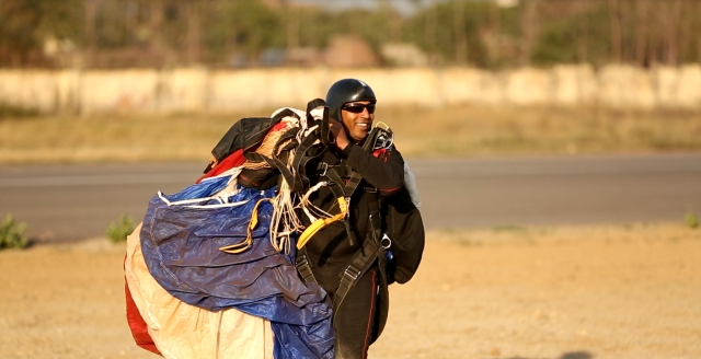 Tandem master, Rajkumar, gathers his parachute after landing. (Photo: <b>The Quint</b>)