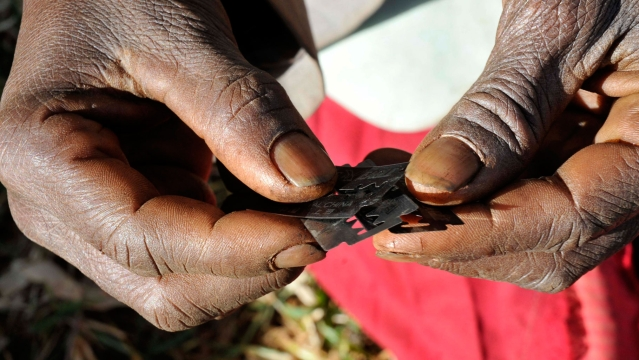 A traditional surgeon holds razor blades before carrying out female genital mutilation on teenage girls from the Sebei tribe in Uganda. (Photo: Reuters)