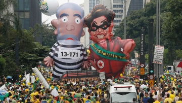 "Demonstrators parade large inflatable dolls depicting Brazil's former President Luiz Inacio Lula da Silva in prison garb and current President Dilma Rousseff dressed as a thief, with a presidential sash that reads ""Impeachment,"" in Sao Paulo, Brazil, 13 March 2016. (Photo: AP)"