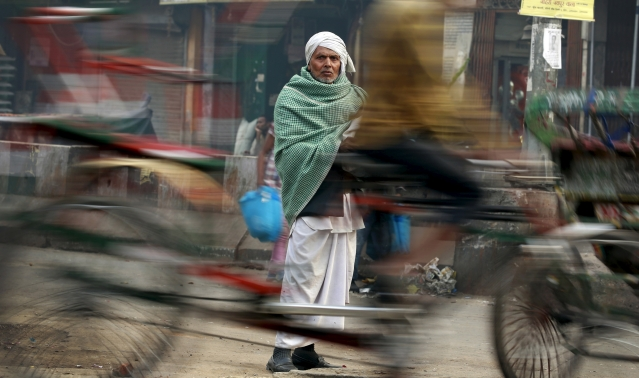 A man looks on as a rickshaw passes by at a busy market in the old quarters of Delhi, 29 February 2016. (Photo: Reuters/Cathal McNaughton)