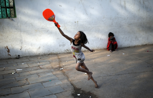 A child plays with a plastic badminton racket in the old quarters of Delhi, 3 March 2016. (Photo: Reuters/Anindito Mukherjee)