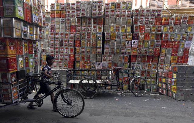 A man pushes a bicycle loaded with empty cooking oil containers at a road side workshop in Kolkata, 2 March 2016. (Photo: Reuters/Rupak De Chowdhuri)