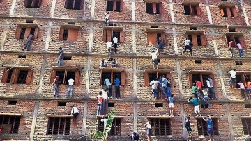 In this file photo, kin of class X examinees climbed many floors to pass on books and chits in Bihar. (Photo: AP)