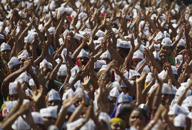 Members of the Patel community raise their arms as they attend a protest rally at Mahesana town, in Gujarat. Thousands of community members on Sunday held a protest rally to demand reservation for their community. (Photo: Reuters/Amit Dave)