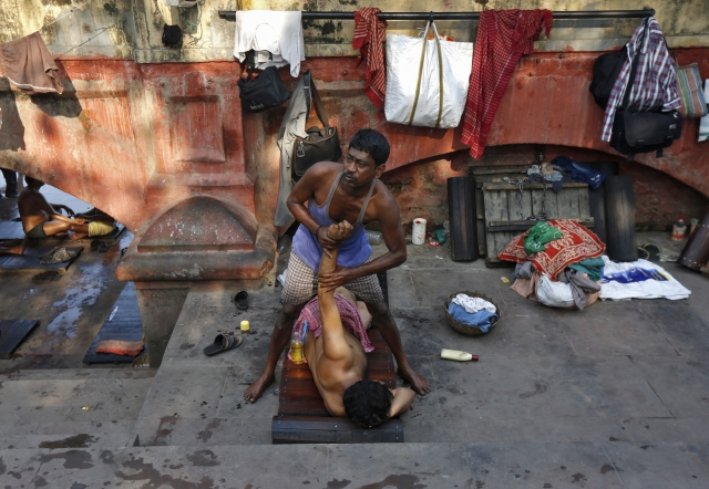A masseur gives a massage to a customer on the banks of the river Ganges in Kolkata, 3 March 2016. (Photo: Reuters/Rupak De Chowdhuri)