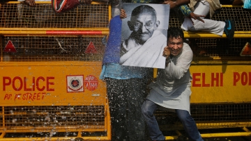 A Congress worker holds a portrait of Mahatma Gandhi as police use water canons to stop protesters from marching towards Parliament during a protest in New Delhi, 2 March 2016. (Photo: AP Photo/Altaf Qadri)