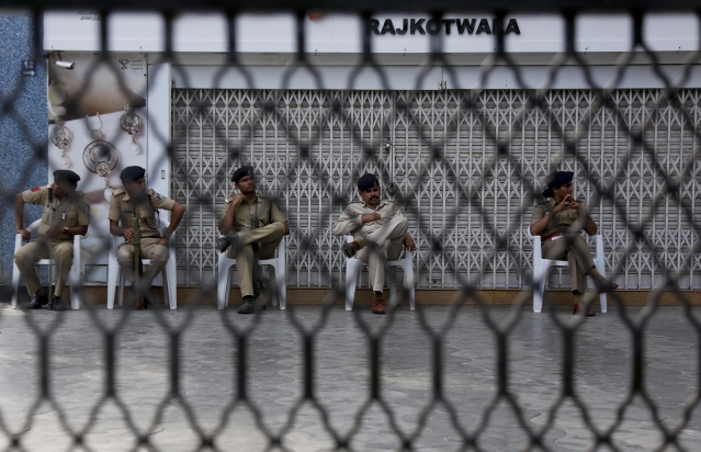 Policemen sit in front of a closed jewellery shop during a strike in Ahmadabad. Jewellers across the country had decided to go on a three-day strike from Wednesday to protest the proposed re-imposition of 1 percent excise duty. (Photo: AP Photo/Ajit Solanki)