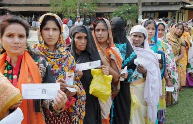 Voters stand  in queue to cast votes at a polling booth during the second phase of state assembly elections in Baska, Assam on Monday. (Photo: PTI)