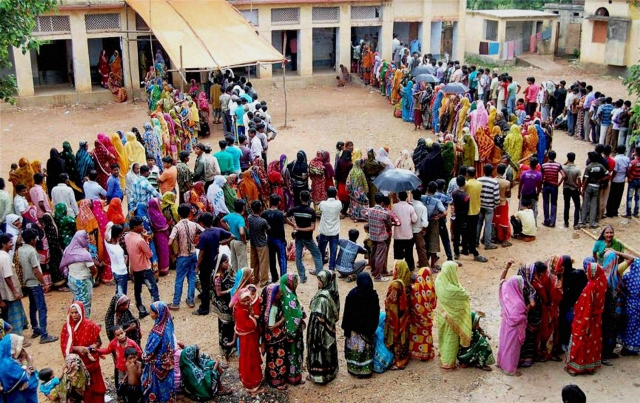 Voters  stand in a long queue to cast their votes at a polling station during the 2nd part of 1st phase West Bengal Assembly Elections in Bankura. (Photo: PTI)