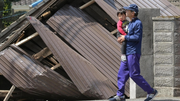 A man with a child, walks past houses destroyed by Thursday's earthquake in Mashiki, Kumamoto. (Photo: AP)