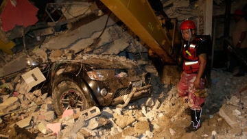 A rescue worker searches in the rubble of a destroyed house in the Pacific coastal town of Pedernales, Ecuador on Sunday. (Photo: AP)