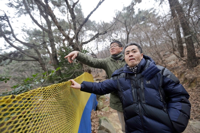 Choi Seung-woo (R) and Lee Chae-sik (L) talk as they walk up a hill behind a row of apartments that was once the Brothers Home in Busan, South Korea, 28 Jan 2016. (Photo: AP)