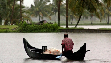A fisherman rowing his boat during monsoons in Alleppy, Kerala. (Photo: Reuters)