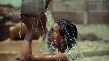 A boy splashes water on himself during a hot day. (Photo: iStockPhoto)