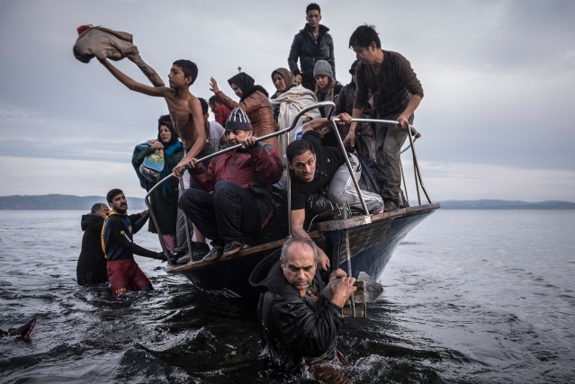 In this 1 November 2015 photo by Sergey Ponomarev, migrants arrive by a Turkish boat near the village of Skala, on the Greek island of Lesbos. Ponomarev, Mauricio Lima, Tyler Hicks and Daniel Etter, of <i>The New York Times</i>, won the <i>Pulitzer Prize</i> for breaking news photography for photographs that captured the resolve of refugees. (Photo: AP)