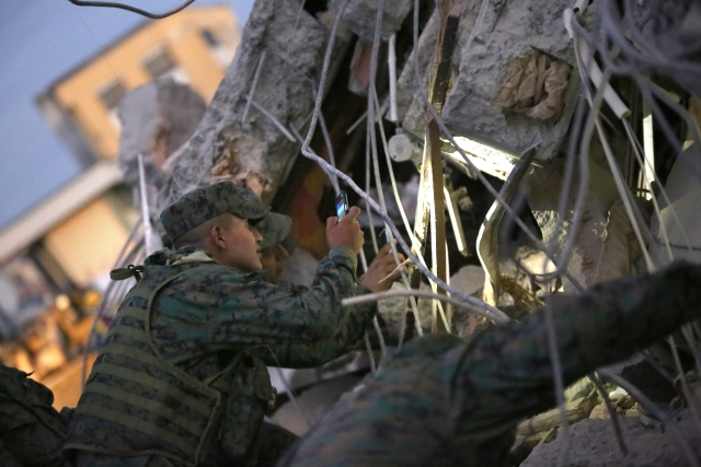 A soldier uses his mobile phone as a flashlight to search for survivors after an earthquake in Portoviejo, Ecuador. (Photo: AP)