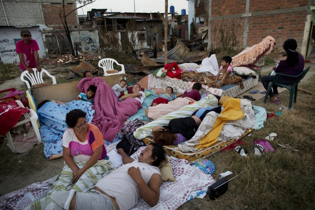 Four families wake up after sleeping outside their homes that collapsed during the earthquake in Manta, Ecuador. (Photo: AP)