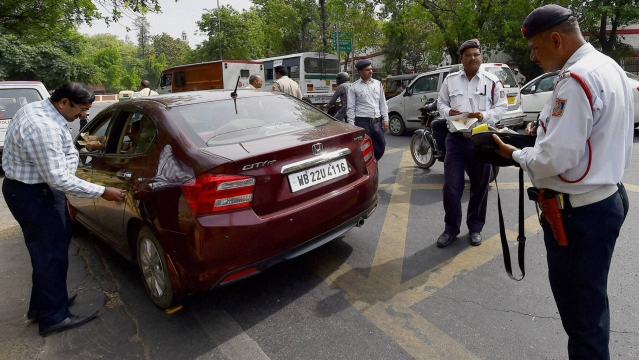 Traffic police men slap a challan to a commuter for riding with number plate ending with an even digit in New Delhi  on the first day of the second phase of  odd-even scheme. (Photo: PTI)