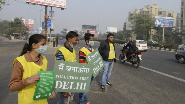 Civil defence volunteers stand on Delhi roads holding placards on the Day-5 of implementation of state government's odd even formula in the national capital on January 5, 2016. (Photo: IANS)