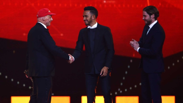 Niki Lauda with his Laureus Lifetime Achievement Award shakes the hand of Formula 1 driver Lewis Hamilton of Mercedes as actor Daniel Bruhl stands by on stage during the 2016 Laureus World Sports Awards (Photo by Tom Dulat/Getty Images for Laureus)