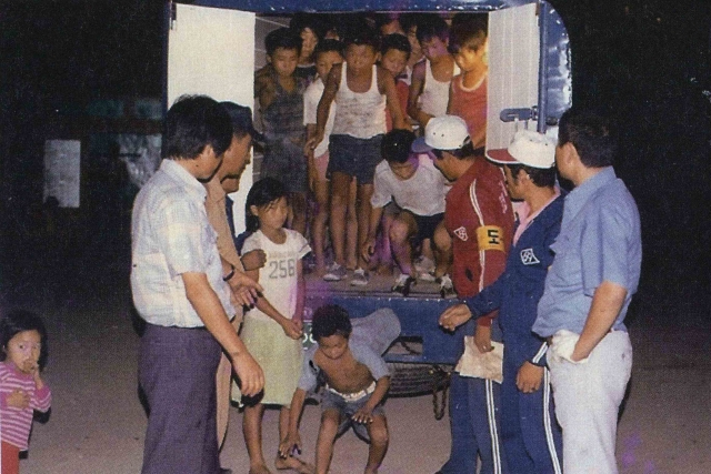 In this undated image provided by the Committee Against Institutionalizing Disabled Persons, a civic group representing the former inmates at the Brothers Home, guards unload children from a truck in Busan, South Korea. (Photo: AP)