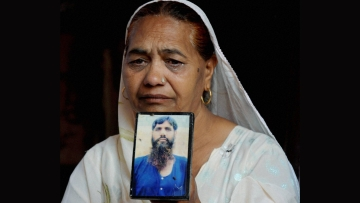 Jagir Kaur,  Kirpal Singh's sister cries as she shows his photograph while mourning the news of his death, in Amritsar, on Tuesday. (Photo: PTI)