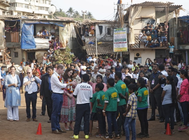 Britain's Prince William, and his wife Kate, the Duchess of Cambridge, talk to children during their visit to a slum in Mumbai. (Photo: AP)