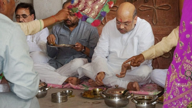 BJP President Amit Shah having a meal with a dalit family in Varansi.