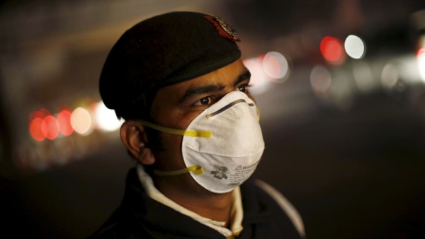 A traffic policeman wears a mask to protect himself from dust and air pollution as he stands on a road-divider in New Delhi, 23 December  2015. (Photo: Reuters)