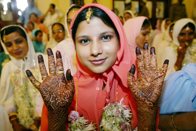 A young Muslim bride belonging to the Dawoodi Bohra community displays her henna-painted palms while waiting for proceedings during a mass wedding in Mumbai. (Photo: Reuters)