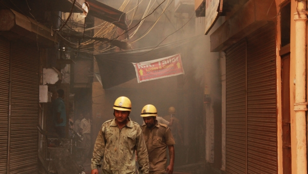 Fire-fighters under a smoking building in Chawri Bazar.