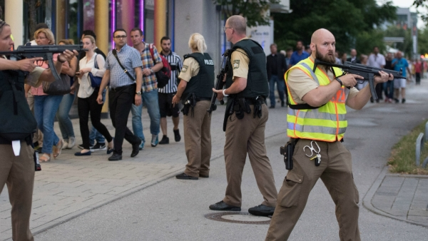 Police escort people who leave the Olympia mall in Munich after shots were fired. (Photo: AP)