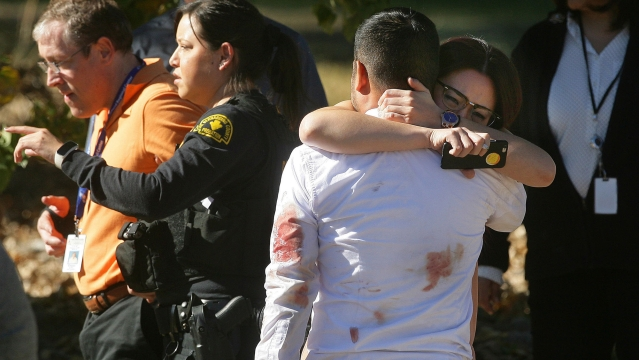 A couple embraces following the California shooting that killed multiple people at a social services facility. (Photo: AP)