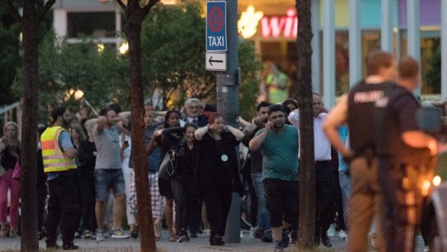 People leave the Olympia mall in Munich. (Photo: AP)