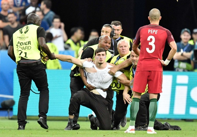 Stewards stop a man that ran on the pitch during the Euro 2016 final. (Photo: AP)