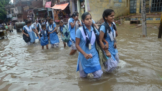 Schoolgirls wade through a water logged street after heavy rains in Mirzapur in early July.