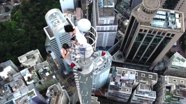 Thrill seekers on top of the 240-metre high building in Hong Kong. (Photo: AP Screengrab)