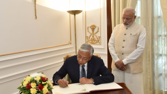Prime Minister Narendra Modi looks on as President of Myanmar, Htin Kyaw signs the visitors book, at Hyderabad House, in New Delhi on 29 August 2016. (Photo: IANS/PIB)