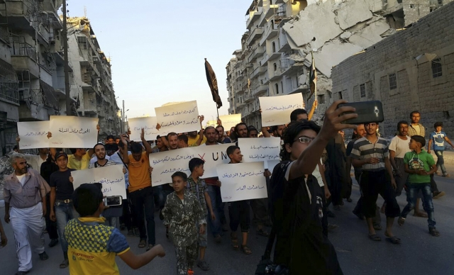In a file photo from 13 September, activists in Syria's besieged Aleppo protest against the United Nations for what they say is its failure to lift the siege off their rebel-held area. (Photo: AP)